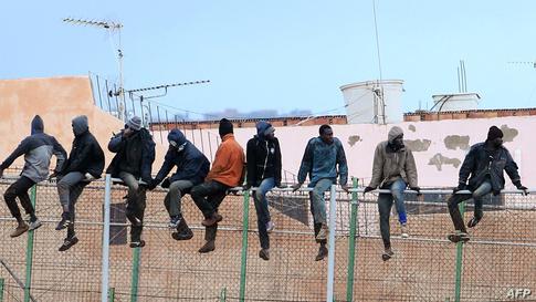 مهاجرون فوق جدار يفصل بين الجانب المغربي مدينة مليلية الخاضة للسيادة الإسبانية