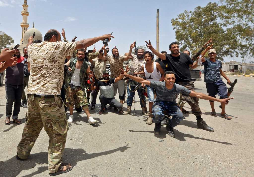Fighters loyal to the UN-recognised Libyan Government of National Accord (GNA) pose for a group picture as they celebrate…