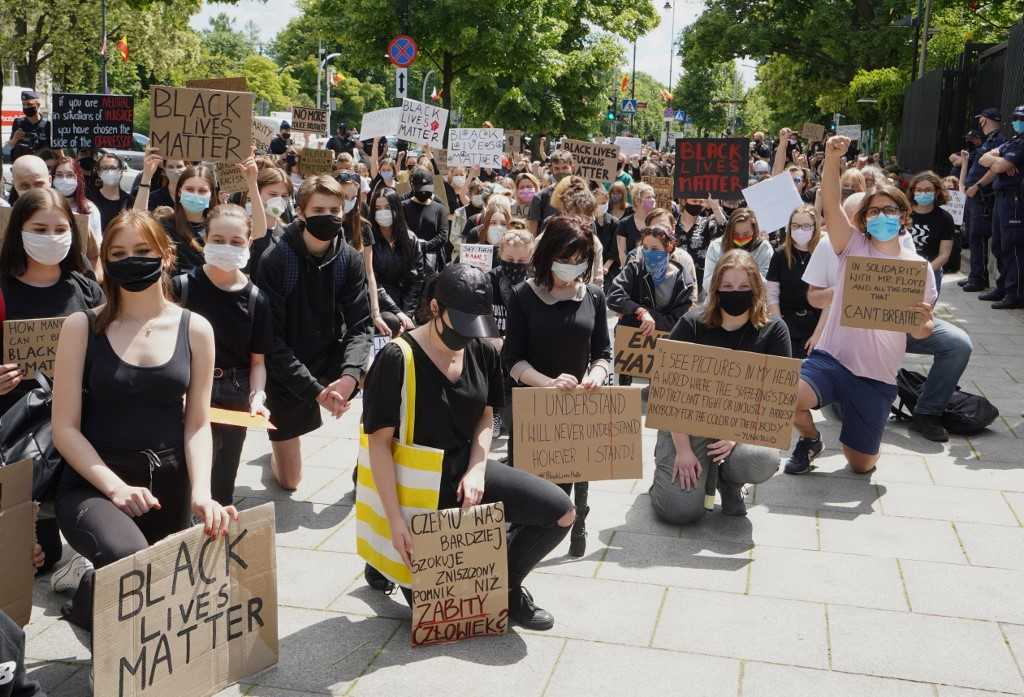 Demonstrators kneel down in protest and hold banners against racism in front of the US embassy in Warsaw on June 4, 2020 in…