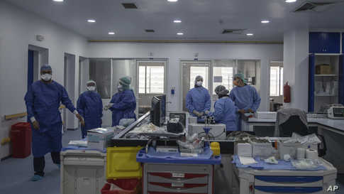 In this photo taken on Wednesday, April 15, 2020, healthcare workers stand inside one of the COVID-19 intensive care units (ICU…