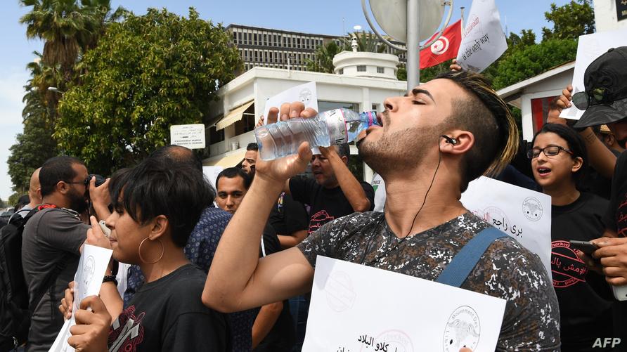 شاب تونسي يشرب المياه خلال تظاهرة للتنديد باعتقال غير الصائمين في شهر رمضان