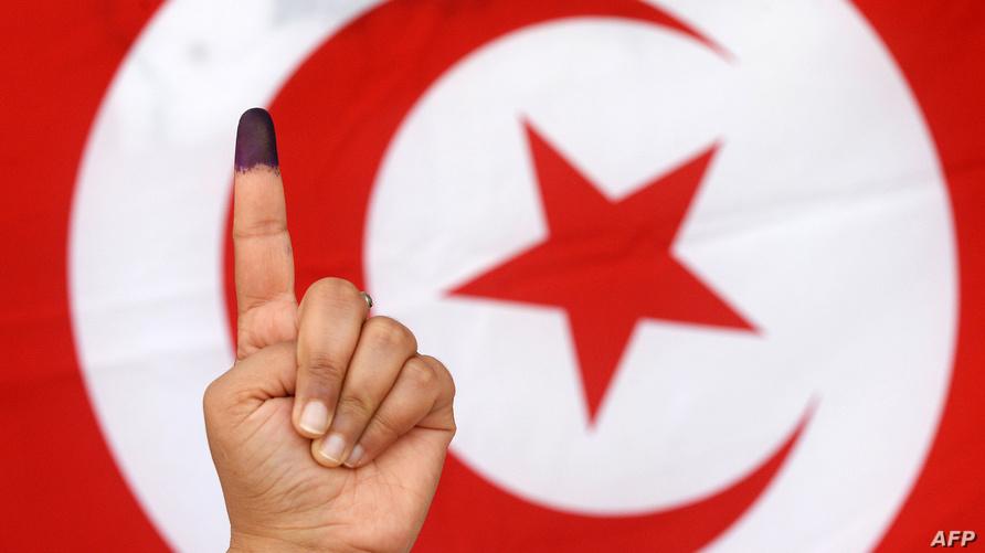 سيدة تونسية تلوح بعد أن أدلت بصوتها في انتخابات عام 2014 (أرشيف)
