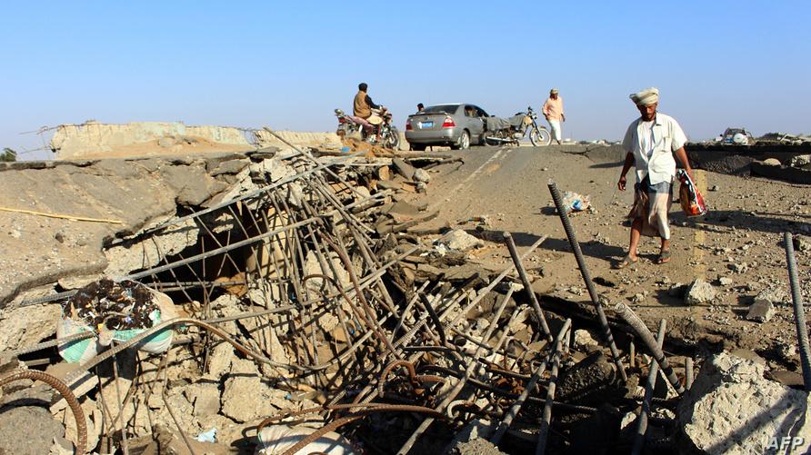 يمنيون في موقع تعرض للقصف في اليمن