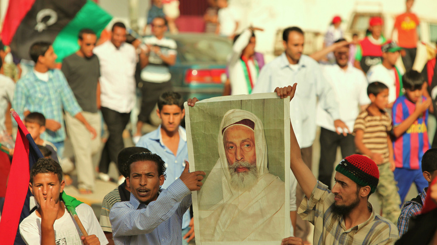 ليبيون في مدينة البيضاء يرفعون صورة الملك الراحل إدريس السنوسي أثناء تظاهرهم ضد نظام العقيد الراحل معمر القذافي