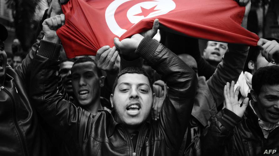 شباب يحملون العلم التونسي خلال احتجاجات 2011