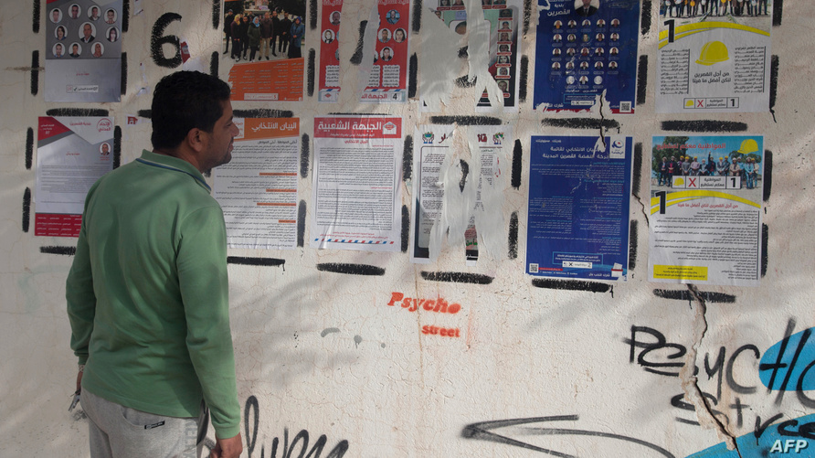 تونسي يقرأ إعلانا انتخابيا - أرشيف