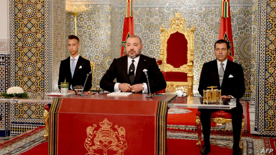 ملك المغرب محمد السادس وعلى يمينه نجله الأمير الحسن، ويسارا الأمير رشيد