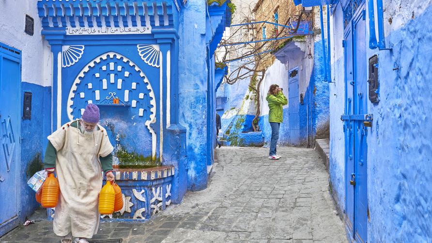 مغربي يحمل عبوات مياه في أحد أزقة مدينة شفشاون (2015)