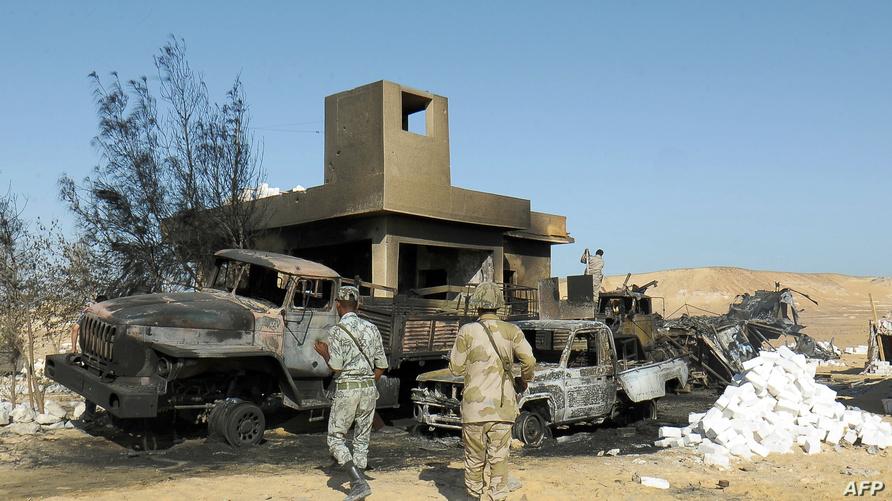 عناصر من الجيش المصري يتفقدون موقع هجوم سابق بالقرب من الحدود مع ليبيا