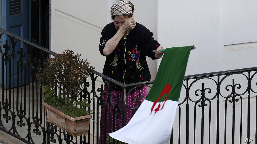 سيدة تساند تظاهرة للحراك برفع العلم الجزائري من شرفة بيتها - أرشيف