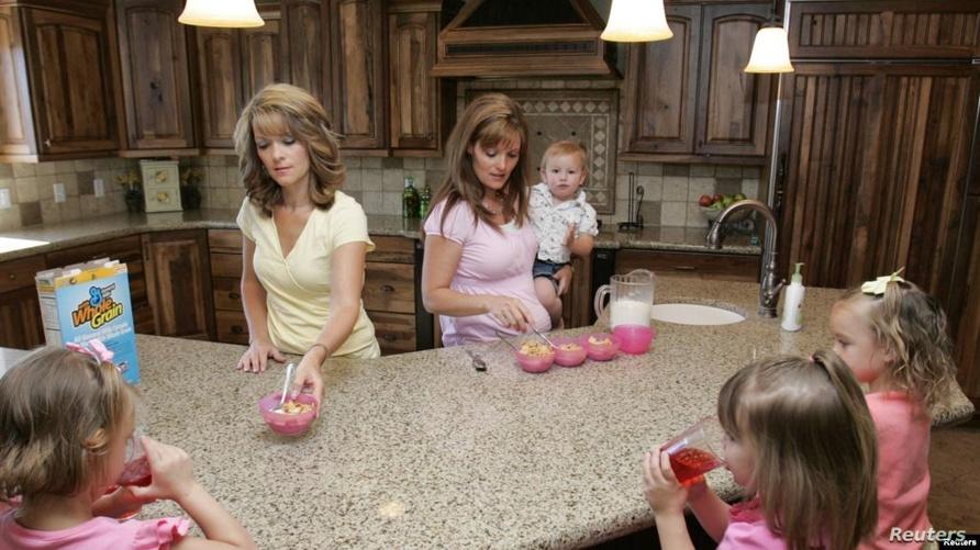 """""""ضرتان"""" من طائفة المورمون يقدمان الطعام لأطفالهما في إحدى منازل يوتا الأميركية.. تمارس بعض الأسر هذا الزواج خفية"""