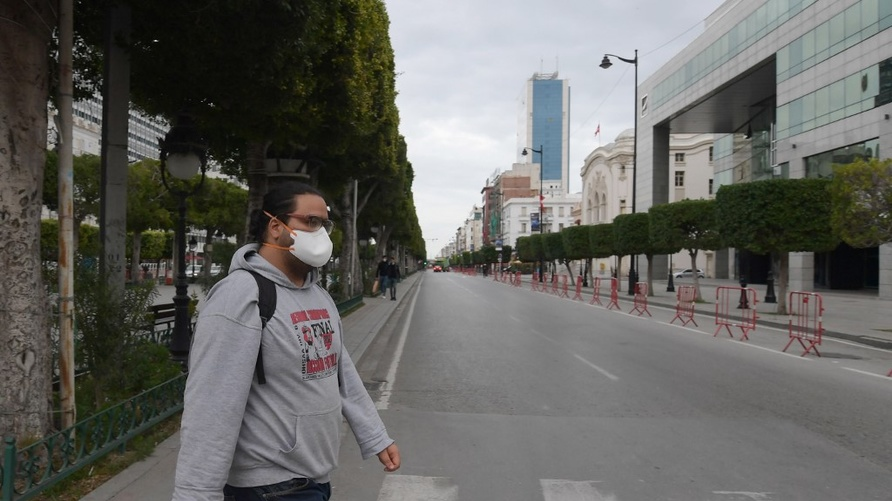 A man wearing a face mask crosses a street at Habib Bourguiba Avenue in Tunis on March 18, 2020 shortly before a night curfew…