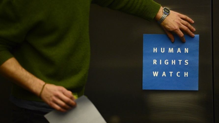 A man puts a logo of US-based rights group Human Rights Watch on the wall as he prepares the room before their press conference…