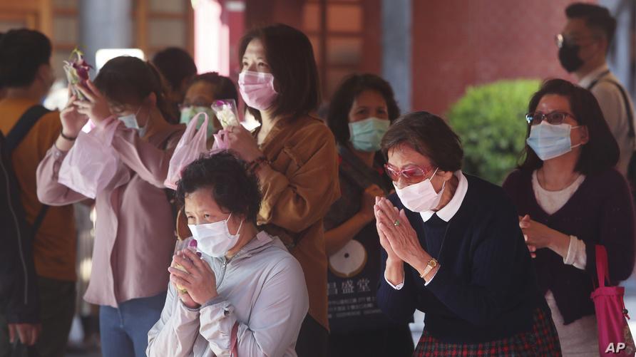 أشخاص يضعون أقنعة واقية داخل معبد في تايوان