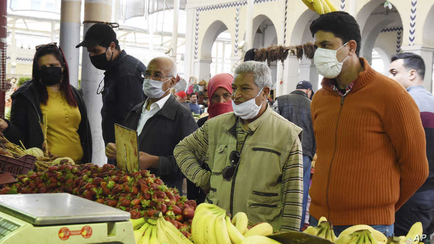 Residents wearing face masks shop for the Ramadan in Tunis, Thursday, April 23, 2020. The Ramadan begins with the new moon…