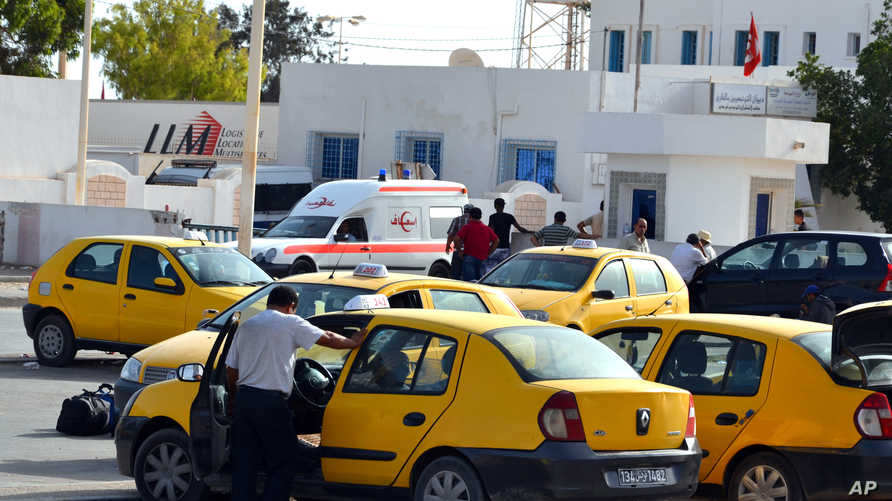Tunisian taxi drivers wait for clients fleeing from Libya at the Ras Ajdir border post between Libya and Tunisia, southern…