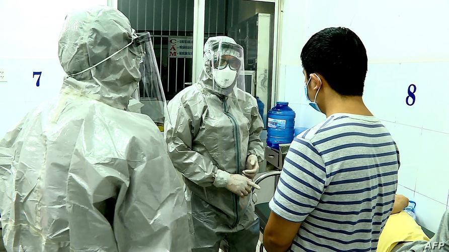 إطاران طبيان يرتديان بدلات واقية لفحص مصابين بفيروس كورونا