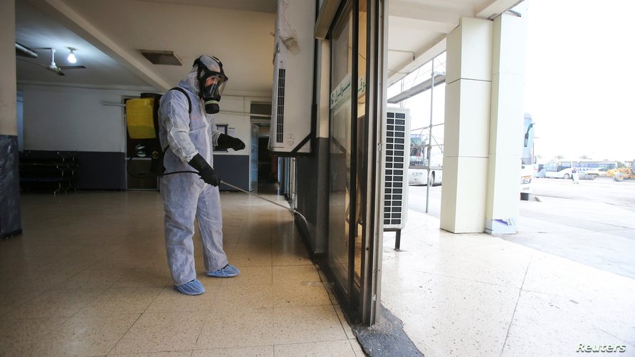 A worker wearing a protective suit disinfects a bus station, following the outbreak of coronavirus disease (COVID-19), in…