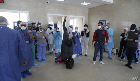 Moroccan patients who recovered from the novel coronavirus disease celebrate with the medical staff as they leave the hospital…