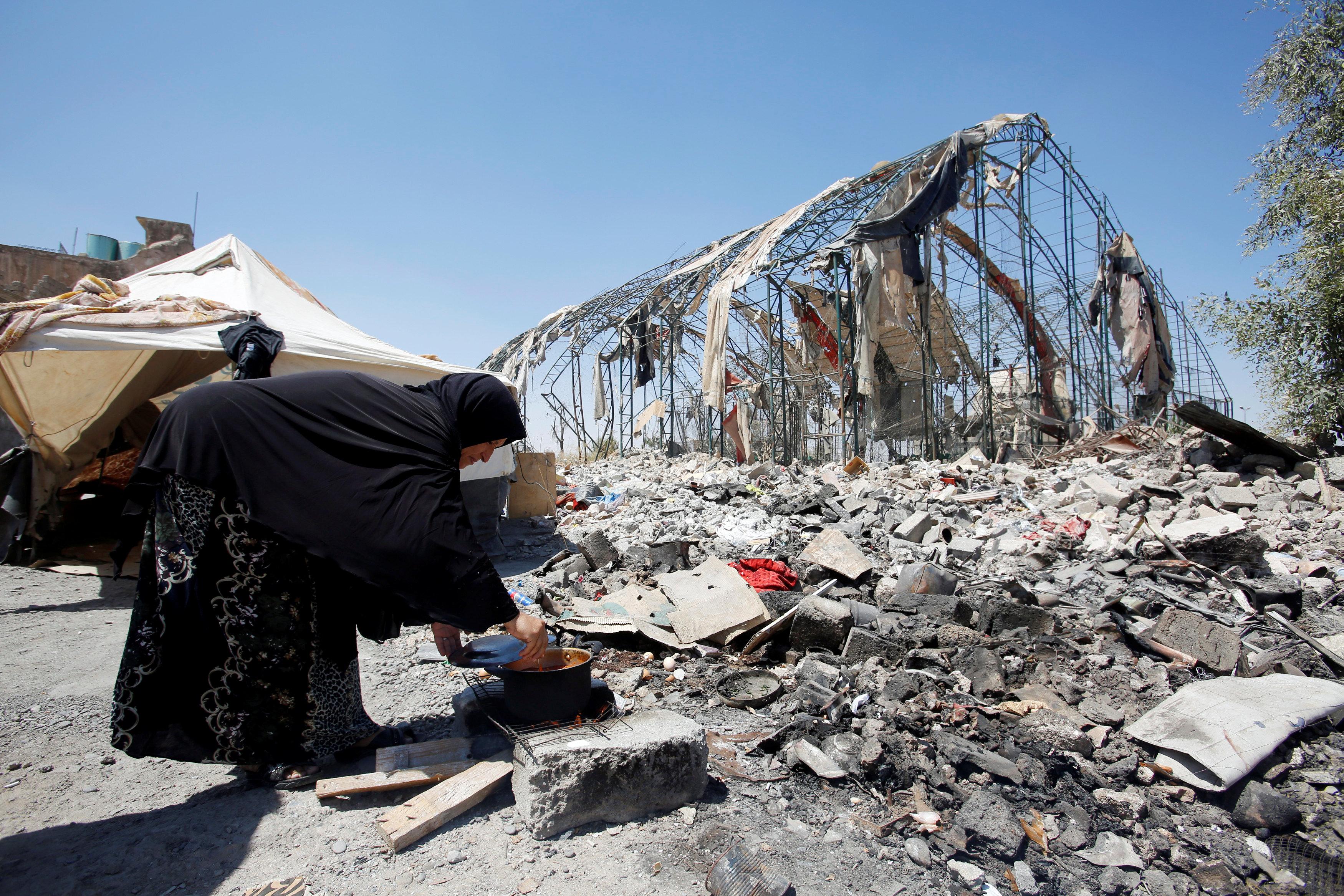 سيدة من الموصل تطهو الطعام على نار بالقرب من أنقاض منزل مهدم