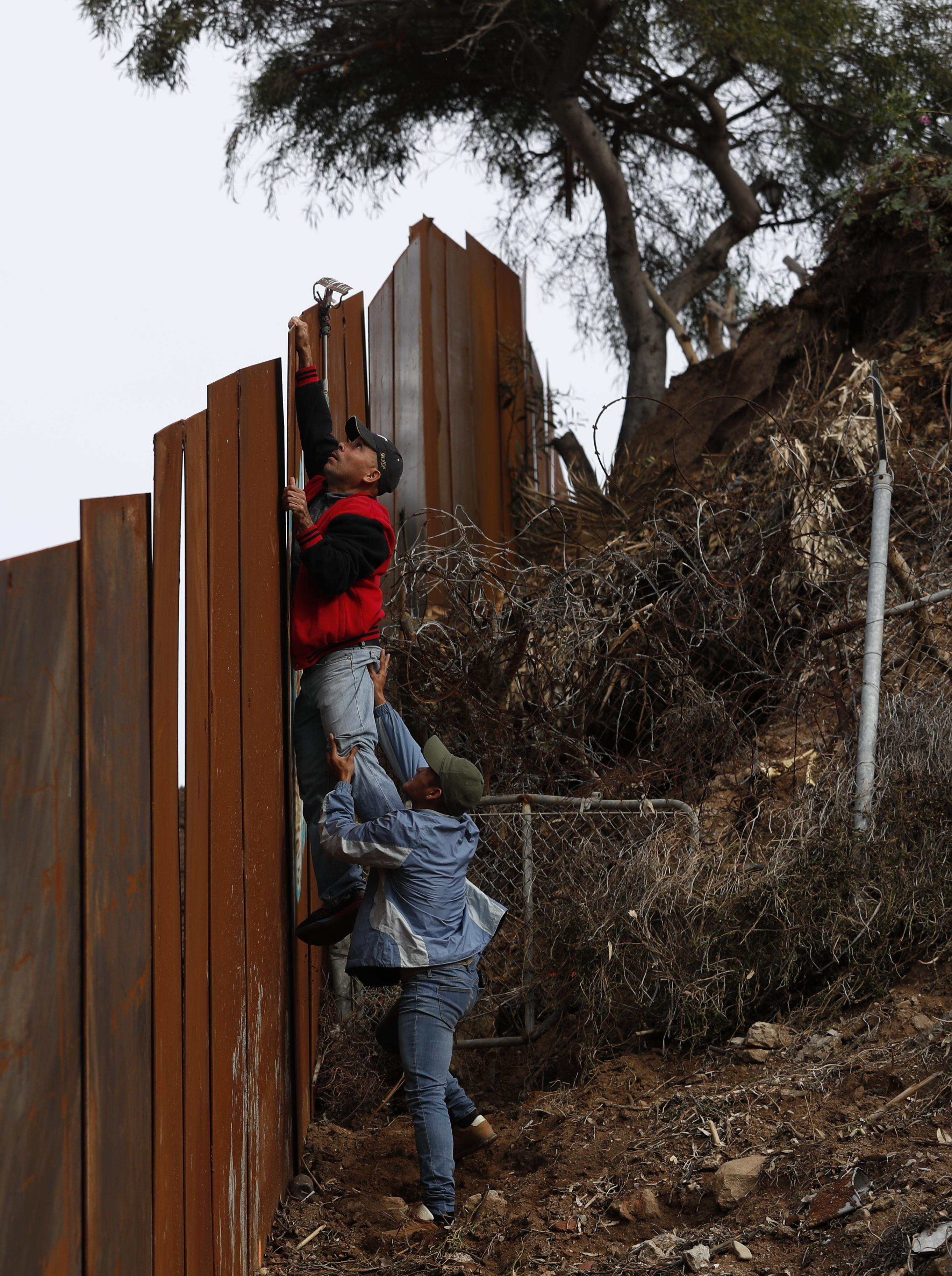 مهاجران من هندوراس يحاولان القفز على جانب من الجدار على الحدود مع المكسيك
