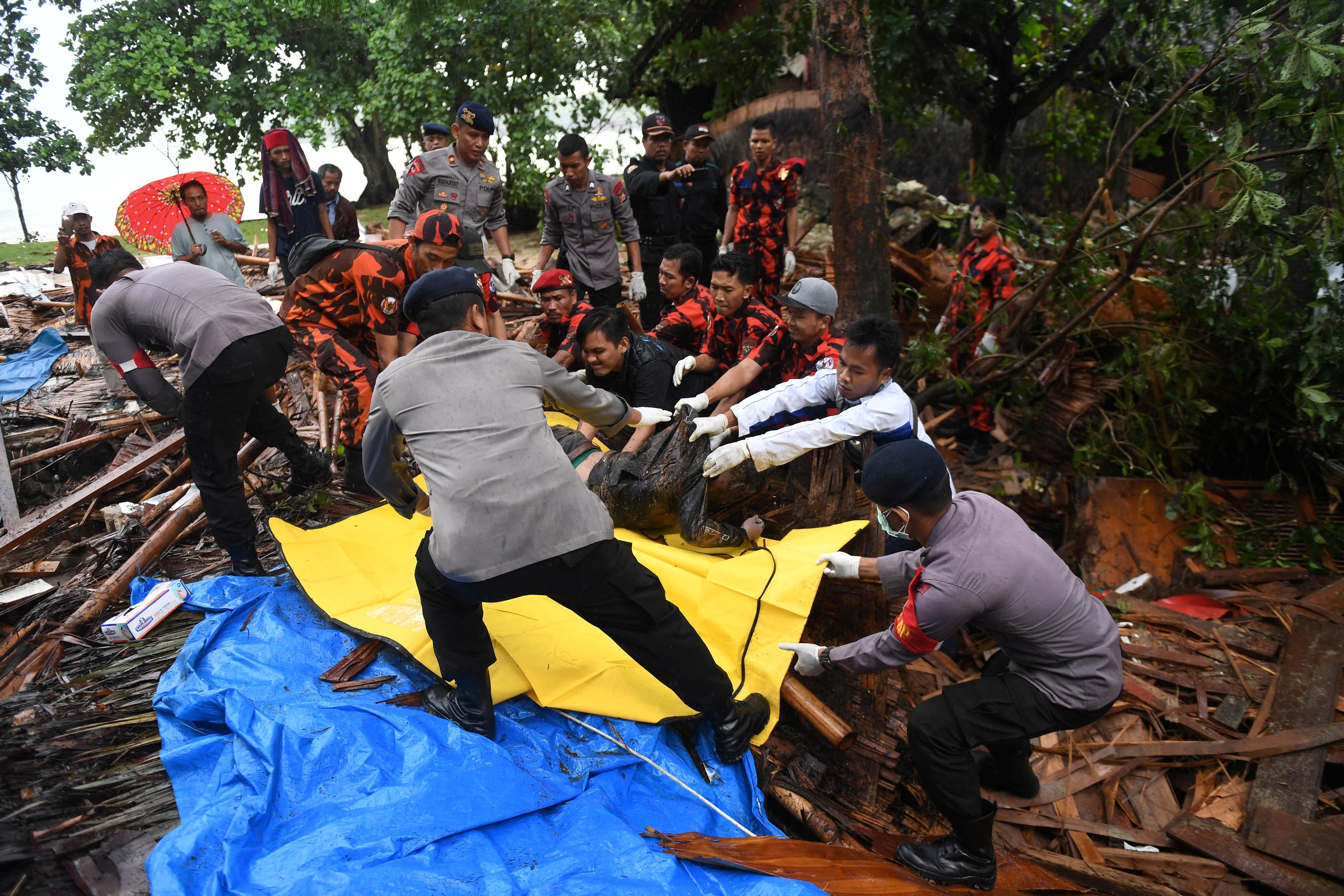 عمال الإنقاذ يحملون جثة أحد الضحايا