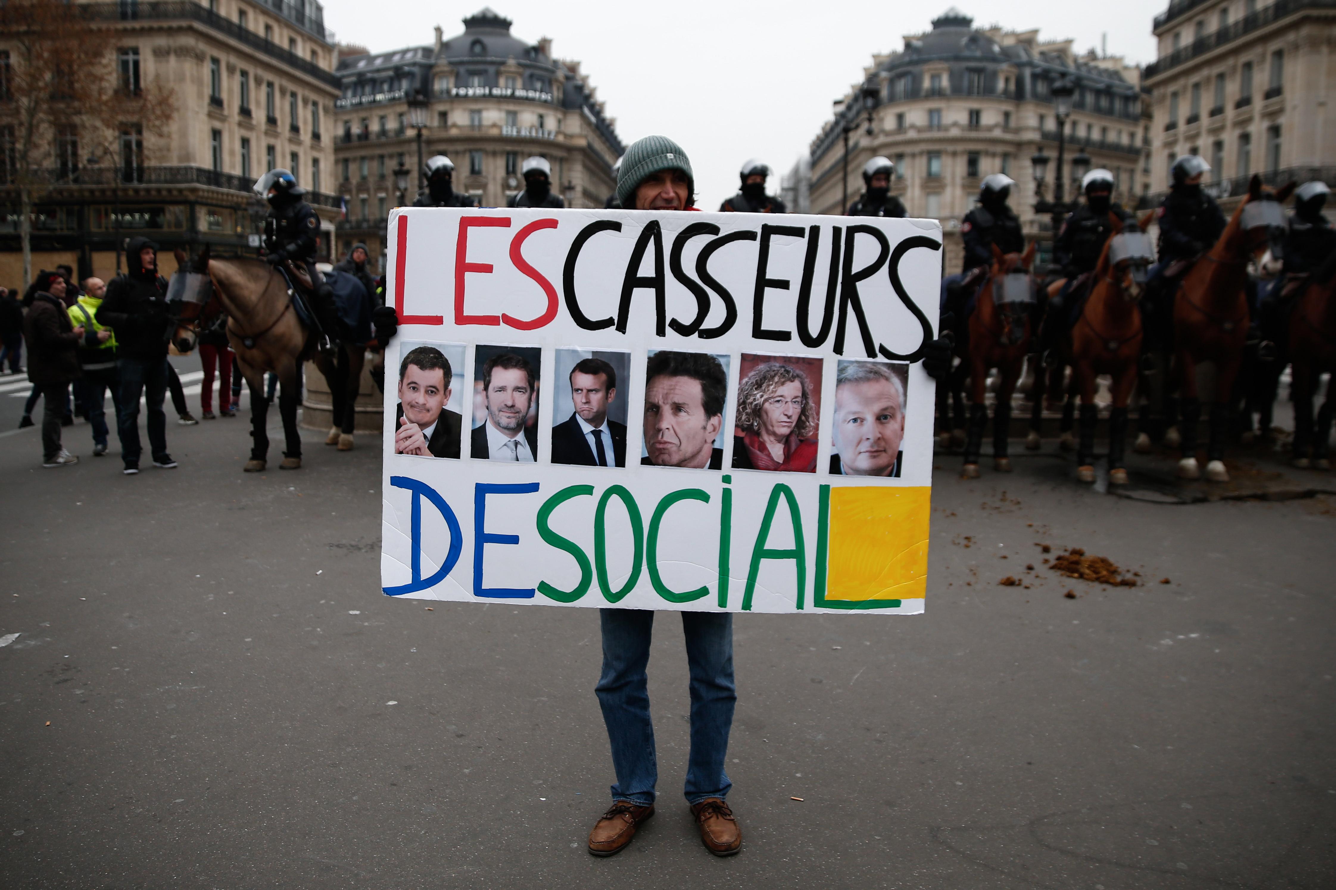 رفع المتظاهرون لافتات تطالب باستقالة الرئيس الفرنسي إيمانويل ماكرون