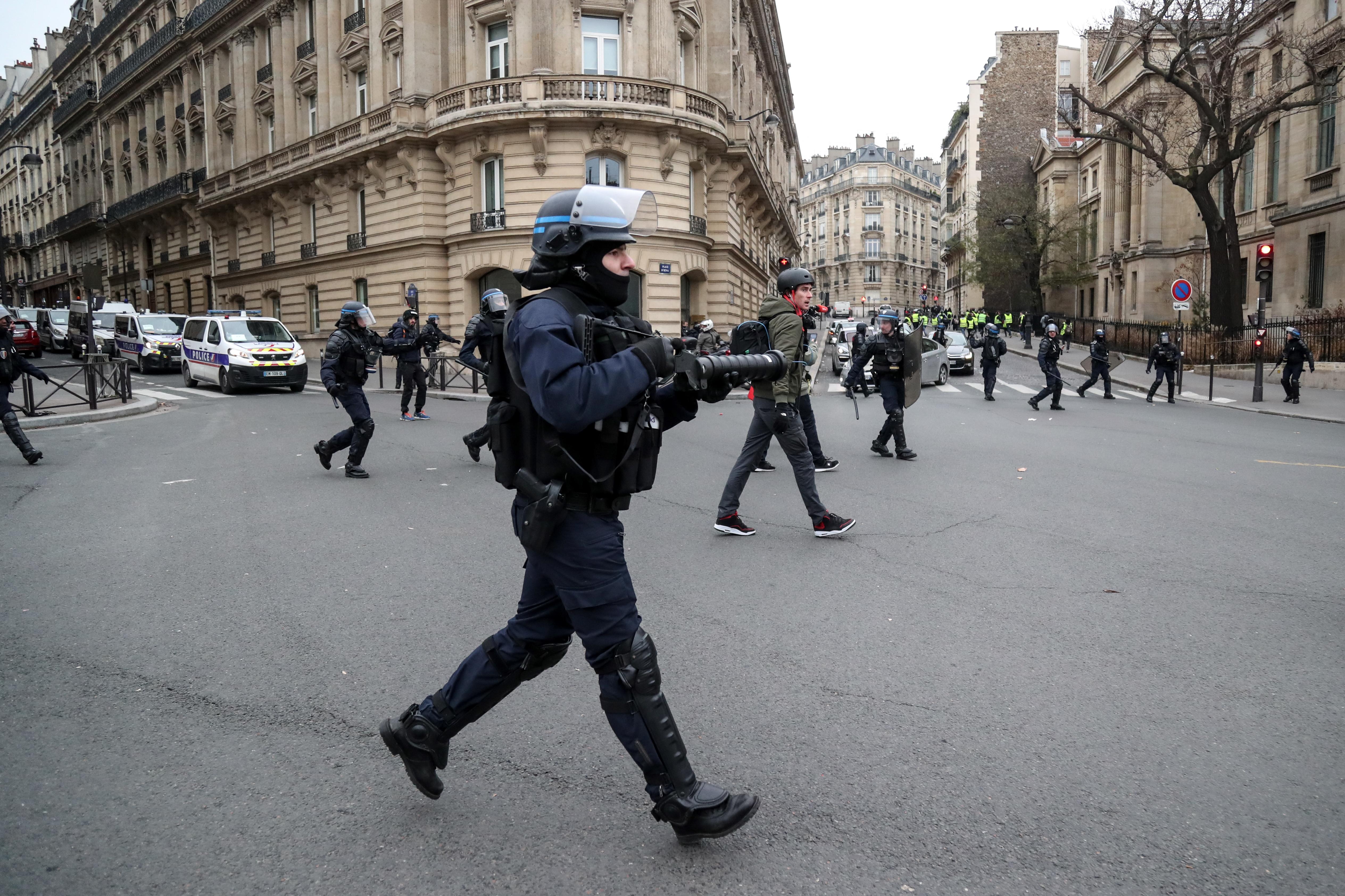 """ضابط شرطة فرنسي يوجه سلاحه غير المميت أثناء تظاهرات """"السترات الصفراء"""" في باريس"""