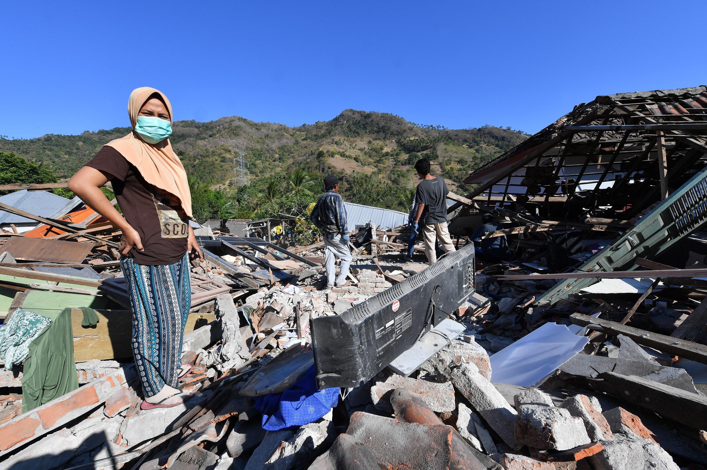 امرأة تقف أمام منزل مدمر جراء زلزال ضرب إندونيسيا