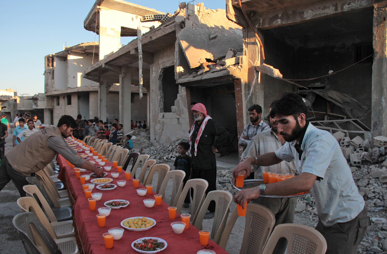 سوريون يتناولون إفطارهم بين حطام الأبنية