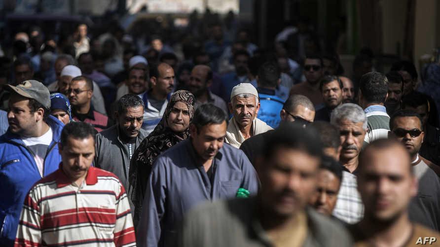 عمال مصريون بعد نهاية ساعات العمل في المحلا شمال القاهرة- أرشيف