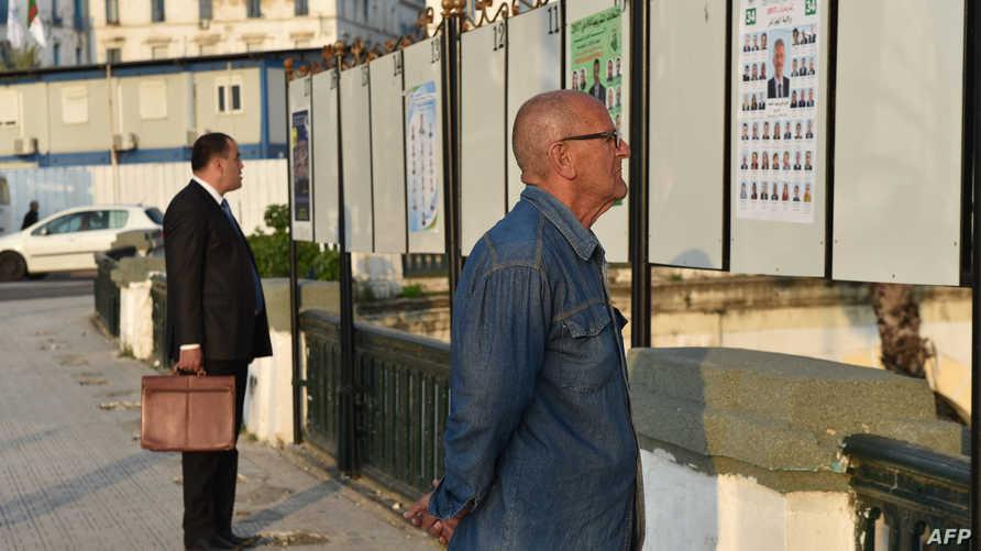 جزائريون ينظرون إلى ملصقات انتخابية