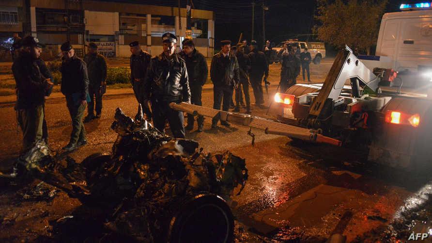 قوى الأمن العراقية تزيل حطام سيارة من موقع انفجار في الموصل