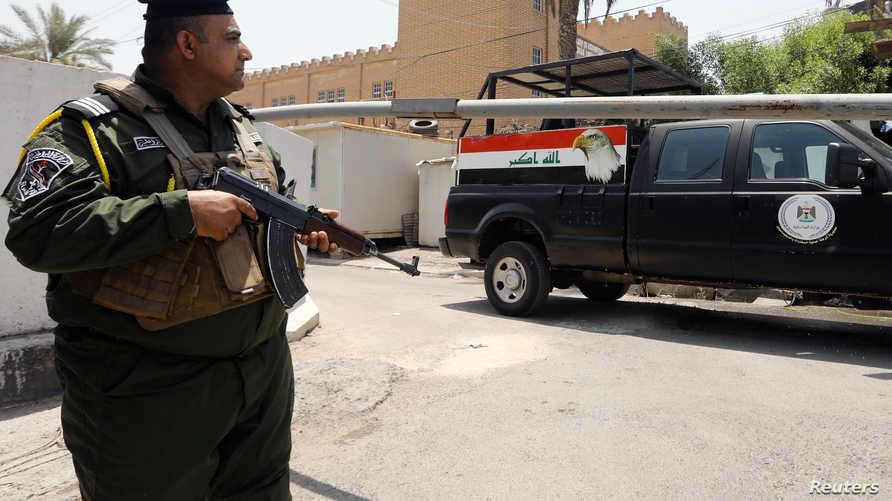 عنصر أمن عراقي يقف أمام مبنى السفارة البحرينية في بغداد