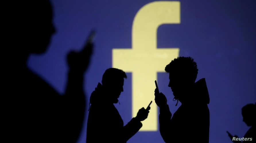 مستخدمو هواتف أمام شعار فيسبوك