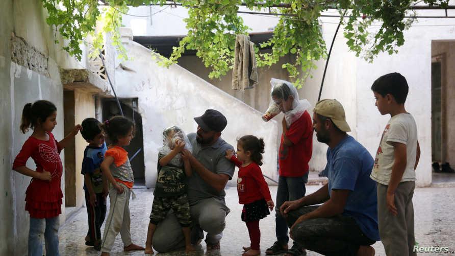أطفال يجربون أقنعة منزلية تحسبا لاستخدام أسلحة كيماوية في إدلب