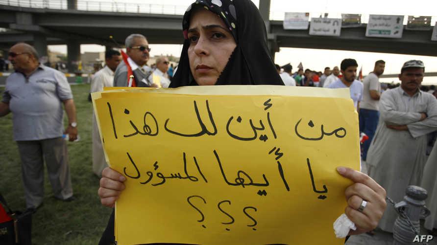 عراقية تحمل لافتة ضد فساد المسؤولين