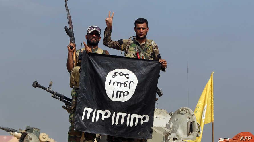 مقاتلان من الحشد الشعبي في بيجي يحملان علم داعش بالمقلوب