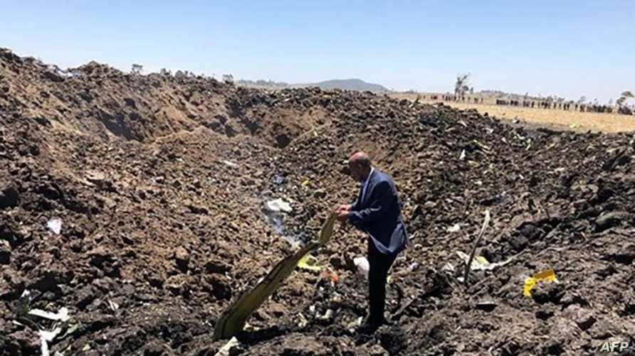 عامل يبحث بين ركام الطائرة الإثيوبية المنكوبة