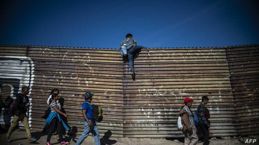 مهاجرون قرب جدار فاصل بين الولايات المتحدة والمكسيك