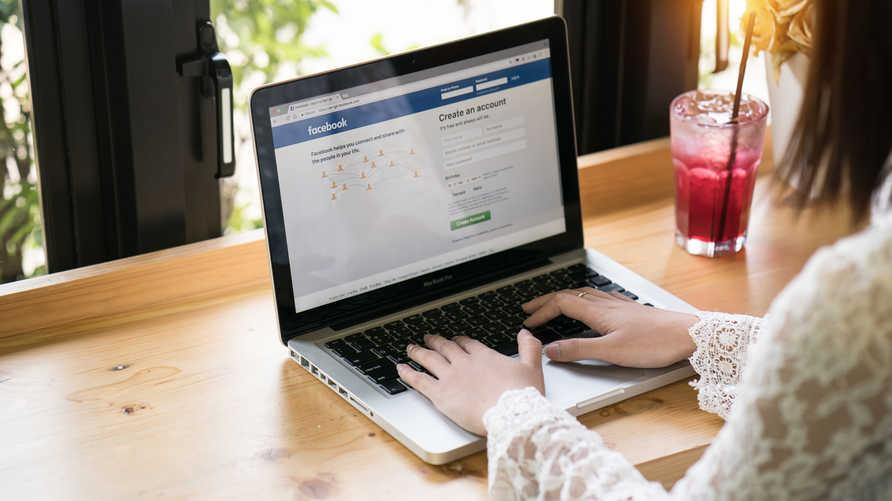 سيدة تحاول الدخول إلى موقع فيسبوك