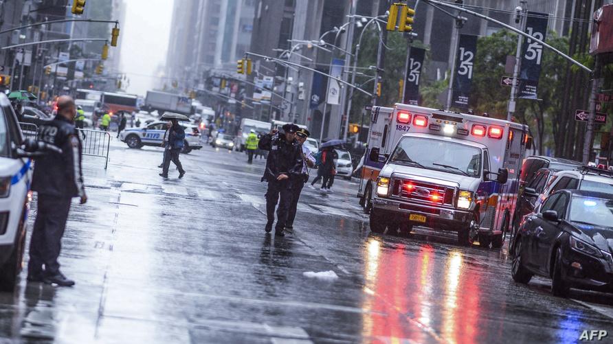شرطي يقف قرب سيارات الطوارئ بعد اصطدام مروحية بمبنى في منهاتن بنيويورك