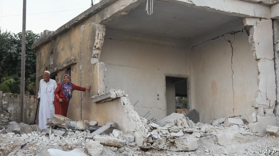 سوريان يتفقدان الأضرار بعد قصف النظام قرية محمبل