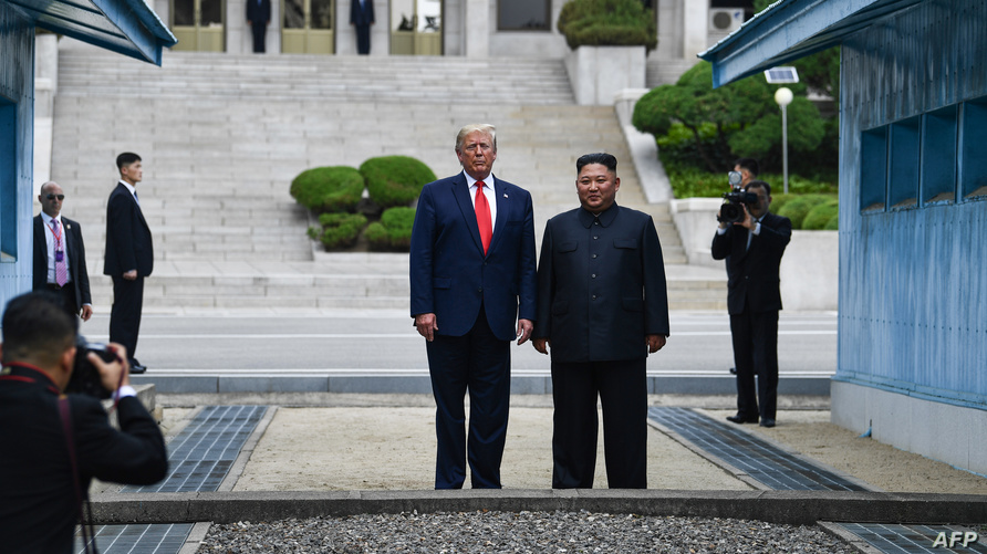 الرئيس الأميركي دونالد ترامب والزعيم الكوري الشمالي كيم جونغ أونغ خلال التقاط الصحفيين صورا لهما في المنطقة منزوعة السلاح
