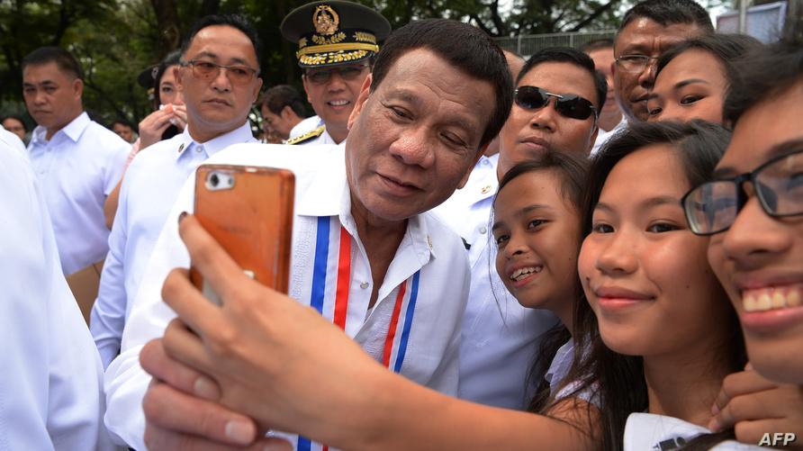الرئيس الفلبيني يلتقط صورة مع طالبات في مانيلا-أرشيف
