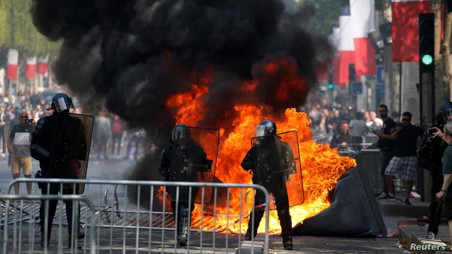 متظاهرون يشعلون النيران في شوارع باريس في العيد الوطني الفرنسي