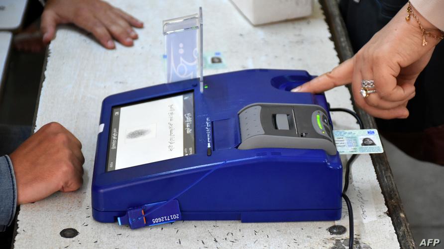 فحص بطاقة الاقتراع البيومترية لناخبة عراقية عند وصولها إلى أحد المراكز الانتخابية في مدينة كركوك