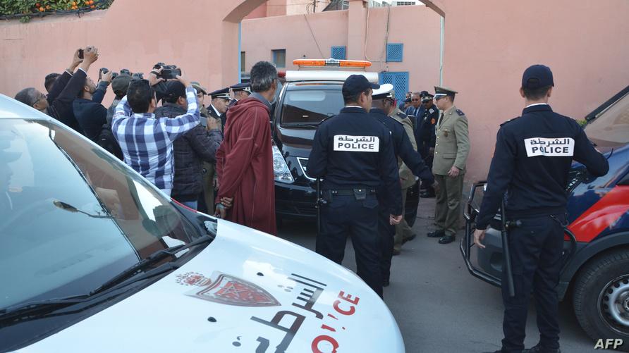 رجال شرطة أثناء نقل جثماني السائحتين