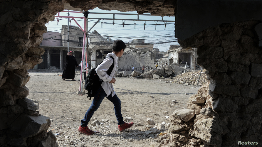 طلاب يسيرون بمدينة الموصل خلال أول يوم دراسي في العراق - 21 أكتوبر 2019