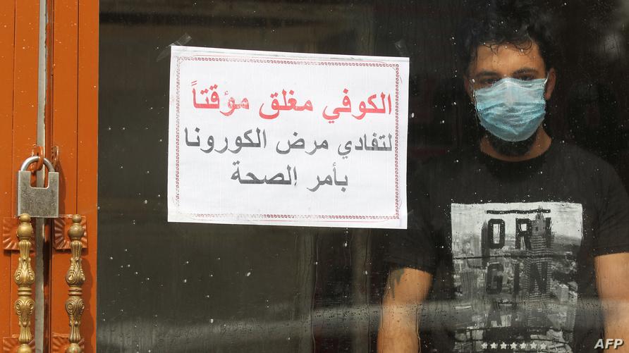 عراقي يرتدي قناعا واقيا يقف داخل مقهى مقفل بسبب فيروس كورونا في العاصمة بغداد